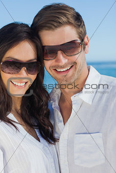 Happy couple wearing sunglasses and smiling at camera