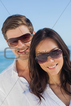 Young couple wearing sunglasses and smiling at camera
