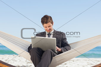 Businessman typing on his laptop in a hammock