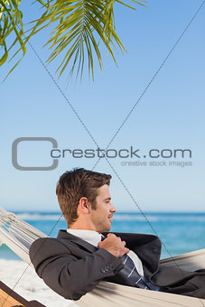 Businessman lying in hammock