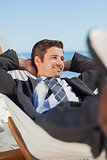 Happy businessman lying in hammock