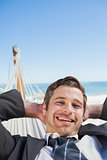 Smiling businessman relaxing in hammock