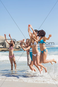 Side view of leaping friends at the beach