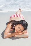 Brunette woman lying down on beach