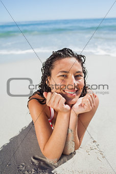 Happy woman lying down on beach