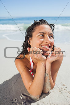 Close up view of smiling woman lying down on beach