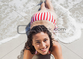 High angle view of smiling woman lying down on beach