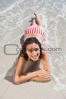 Brunette lying down on beach