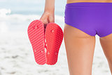 Rear view of a young woman holding flip flops