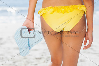 Woman in yellow bikini standing back to camera holding flip flops