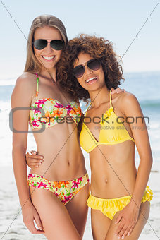 Two pretty friends in bikinis wearing sunglasses posing