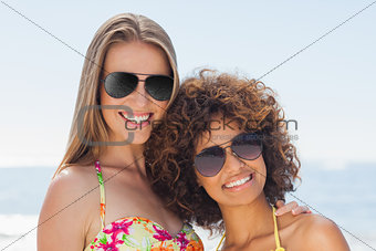 Two friends wearing sunglasses smiling at camera