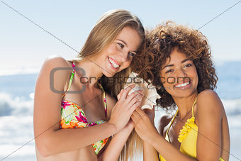 Two girls in bikinis listening to conch shell