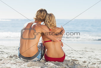 Rear view of a young couple sitting on the beach