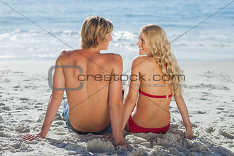Happy couple sitting on beach