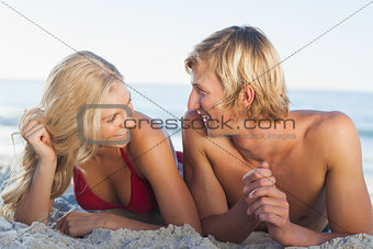 Smiling couple facing each other and lying