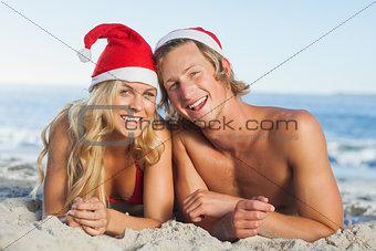 Couple lying on beach wearing christmas hats