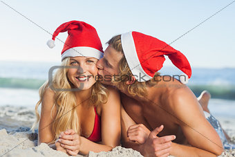 Man giving kiss to partner wearing christmas hats