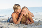 Man covering girlfriends eyes lying on the beach