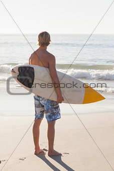 Man with his surfboard on the beach