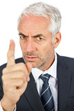 Angry businessman pointing his finger and looking at camera