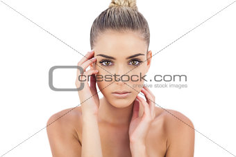 Cute woman holding her head and looking at camera