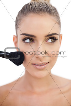 Happy woman applying powder on her cheeks