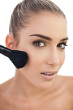 Surprised woman applying powder on her cheeks