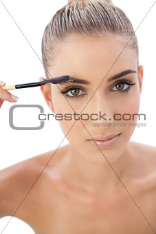 Serious woman applying make up on her eyebrows
