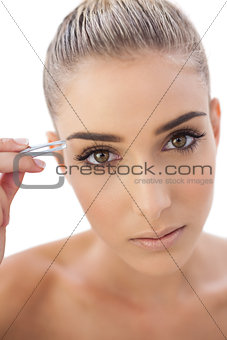 Focused woman plucking her eyebrows