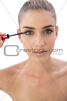 Concentrated woman applying mascara