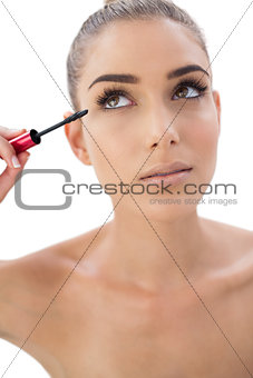 Pensive woman applying mascara