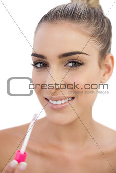 Cheerful woman applying gloss on her lips