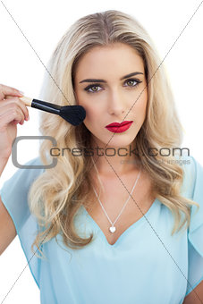Serious blonde model in blue dress applying make up