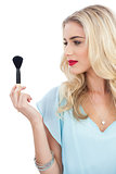 Blonde model in blue dress looking at her blush brush