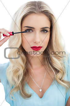 Serious blonde model in blue dress applying mascara