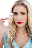 Serious blonde model in blue dress holding a eyelash curler