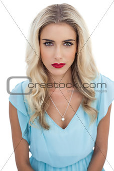 Severe blonde model in blue dress looking at camera