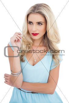 Attractive blonde model in blue dress looking away