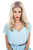 Puzzled blonde model in blue dress looking at camera