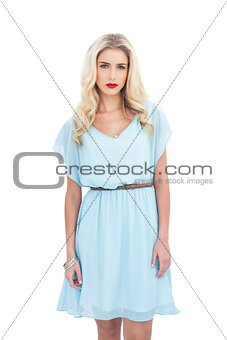 Charming blonde model in blue dress looking at camera