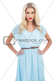 Contemplative blonde model in blue dress posing with hands the on hips
