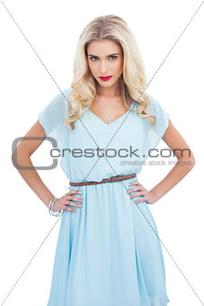 Lovely blonde model in blue dress posing with hands on the hips