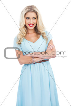 Smiling blonde model in blue dress posing crossed arms