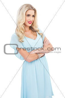 Pleased blonde model in blue dress posing crossed arms
