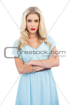Severe blonde model in blue dress posing crossed arms