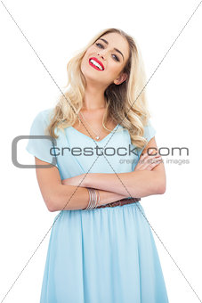 Content blonde model in blue dress posing crossed arms
