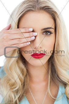 Blonde model in blue dress looking at camera with one eye and hidding the other with her hand