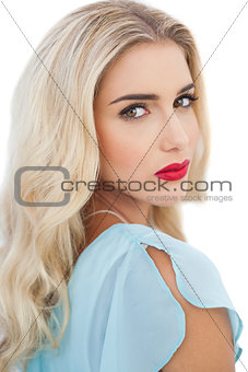 Portrait of a stylish blonde model in blue dress looking at camera