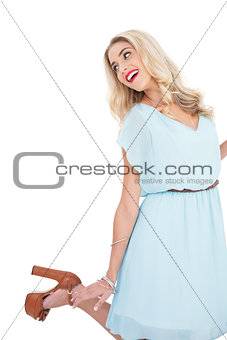 Smiling blonde model in blue dress posing and jumping